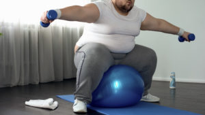 Corpulent male in sportswear lifting dumbbells sitting on fitness ball, activity