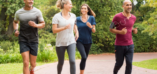 Healthy group of people jogging on track in park. Happy couple enjoying friend time at jogging park while running. Mature friends running