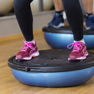 Low section of woman standing on bosu ball in health club