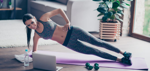 Beautiful sporty cheerful woman is doing side plank exercise. She is watching video on the internet and repeating the tasks