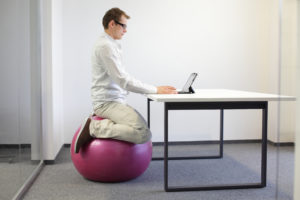 man sitting on stabilit ball