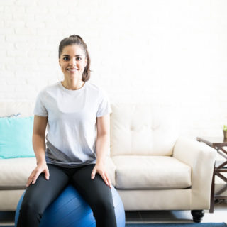 Portrait of smiling young woman sitting on a swiss ball for exercising in her living room