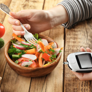 Woman holding digital glucometer while eating salad at table. Diabetes diet