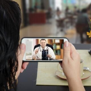 Woman sits at a cafe table and communicates with telemedicine doctor by cellphone. In touchscreen, male physician reviewing brain x-ray image.